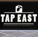 The pub sign. Tap East, Stratford, Greater London